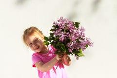 Emozioni del ` s dei bambini Bambino felice con un mazzo del lillà in sue mani Immagini Stock Libere da Diritti