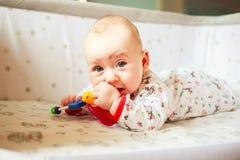 Emozioni del ` s dei bambini Il bambino è a letto e giocando con i giocattoli Un bambino a casa conosce il mondo il bambino impar Immagini Stock Libere da Diritti