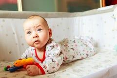 Emozioni del ` s dei bambini Il bambino è a letto e giocando con i giocattoli Un bambino a casa conosce il mondo il bambino impar Fotografia Stock Libera da Diritti