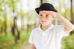 Emozioni di manifestazione del ragazzino al fondo del parco con luce Fotografie Stock Libere da Diritti