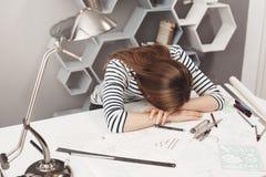 Emozioni negative Ritratto di giovane architetto indipendente femminile alla moda che si trova dopo sulle mani alla tavola, essen Fotografia Stock Libera da Diritti