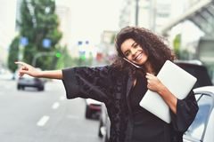 Emozioni positive L'uso felice della donna della corsa mista un telefono, prova prende un taxi immagini stock