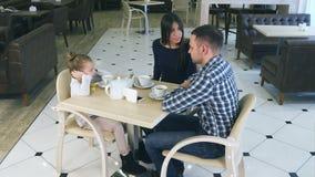 Empörte Mutter, die auf Tochter und Ehemann im Café tadelt Littke-Mädchen, das ihre Ohren schließt stock footage