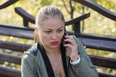 Empörtes, überraschtes Mädchen spricht am Telefon draußen Lizenzfreies Stockbild