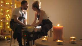 Empañado de hombre y de una mujer que hace el jarro de la arcilla en la rueda de alfarero almacen de video