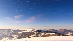 Empañe la mudanza sobre la montaña en invierno con un cielo asteroide almacen de video