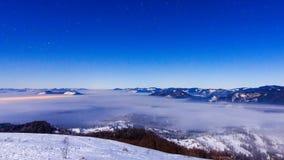 Empañe la mudanza sobre la montaña en invierno con un cielo asteroide metrajes