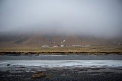 Empañe la nube que viene abajo un valle en Islandia, una línea de pequeñas casas Foto de archivo libre de regalías