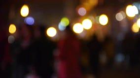 Empañe la silueta ocupada de la muchedumbre y el círculo de la luz de neón en la calle del negocio en la noche almacen de metraje de vídeo