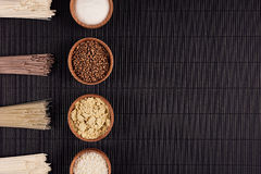 Empacota macarronetes crus com o ingrediente em umas bacias de madeira no fundo listrado preto da esteira com espaço da cópia, vi Fotografia de Stock