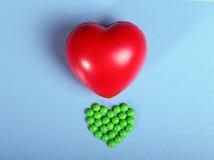 Empacotamento das tabuletas e dos comprimidos na tabela Coração vermelho Imagens de Stock