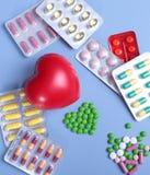Empacotamento das tabuletas e dos comprimidos na tabela Coração vermelho Fotos de Stock Royalty Free
