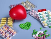 Empacotamento das tabuletas e dos comprimidos na tabela Coração vermelho Imagens de Stock Royalty Free