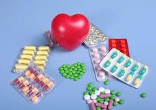 Empacotamento das tabuletas e dos comprimidos na tabela Coração vermelho Fotografia de Stock
