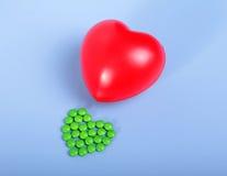 Empacotamento das tabuletas e dos comprimidos na tabela Coração vermelho Fotografia de Stock Royalty Free