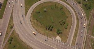 Empalme de camino redondo de la visión superior en la ciudad del smoll en puesta del sol coches activos del tráfico de ciudad Vue almacen de metraje de vídeo