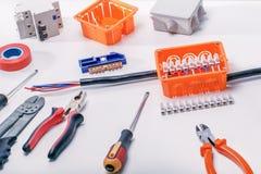 Empalmes eléctricos con los alambres, la caja de conexiones y diversos materiales usados para los trabajos imagen de archivo