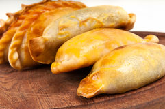 Empanada close up over wooden table. Group of Latin american empanadas over wooden plate. The Empanada is a pastry turnover filled with a variety of savory Stock Images