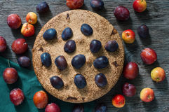 Empanada con el ciruelo y las manzanas La torta en la tabla oscura de madera se adorna con los ciruelos y las manzanas frescos fotografía de archivo