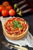 Empanada con las berenjenas, los tomates y el queso en la placa gris adornada con las hojas de la albahaca y las bifurcaciones fr fotografía de archivo