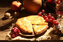 Empanada con queso y aceite, fruta, una nuez y vino rojo Imágenes de archivo libres de regalías