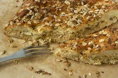 Empanada cortada sabrosa con las semillas y los granos en el top y bifurcación en el papel de pergamino foto de archivo