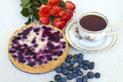Empanada de arándano, taza de té, montón de arándanos y rosas rojas en un fondo blanco - opinión de alto ángulo Fotos de archivo libres de regalías