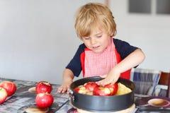 Empanada de ayuda y que cuece del niño pequeño adorable de manzana en el '' kitc casero de s Imagen de archivo libre de regalías