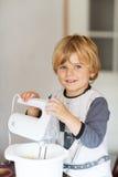Empanada de ayuda y que cuece del niño pequeño adorable de manzana en el '' kitc casero de s Foto de archivo