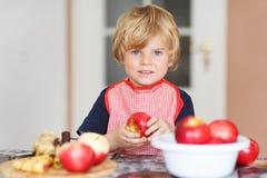 Empanada de ayuda y que cuece del pequeño niño adorable de manzana en el '' ki casero de s Fotografía de archivo libre de regalías