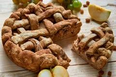 Empanada de manzana hecha en casa de Slised adornada con las manzanas frescas, las uvas y las pasas marrones en fondo de madera l Fotos de archivo
