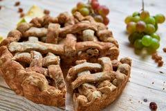 Empanada de manzana hecha en casa de Slised adornada con las manzanas frescas, las uvas y las pasas marrones en fondo de madera l Imagenes de archivo