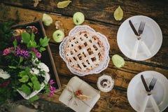 Empanada de manzana, manzanas y hojas de otoño hechas en casa en la tabla de madera Imagenes de archivo