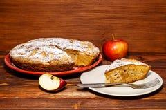 Empanada de manzana recientemente cocida en un fondo rústico de la madera oscura Manzanas frescas y un pedazo de empanada de manz Imágenes de archivo libres de regalías