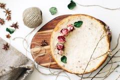 Empanada del requesón y de los plátanos Pastel de queso recientemente cocido en fondo rústico Decoración de flores secadas popula Fotos de archivo