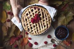 Empanada hecha en casa del otoño con las frambuesas y las bayas En un fondo de madera con las hojas de otoño El cocer para la opi fotografía de archivo