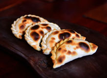 Empanada, meat pie. 4 Empanadas, meat pie, on a dark wood plate. The Empanada is a pastry turnover filled with a variety of savory ingredients and baked or Royalty Free Stock Images