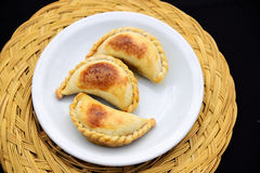 Empanada, meat pie. 3 Empanadas, meat pie, white plate on a Straw mat. The Empanada is a pastry turnover filled with a variety of savory ingredients and baked Stock Photography