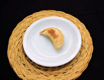 Empanada, meat pie. , white plate on a Straw mat. The Empanada is a pastry turnover filled with a variety of savory ingredients and baked or fried Royalty Free Stock Photography