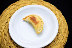 Empanada, meat pie. , white plate on a Straw mat. The Empanada is a pastry turnover filled with a variety of savory ingredients and baked or fried Royalty Free Stock Photos