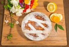 Empanada napolitana de pascua asperjada con el azúcar de formación de hielo y adornada con fresia y frutas frescas Foto de archivo libre de regalías