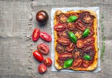 Empanada rústica del otoño del tomate con las hierbas y los tomates frescos en un silv Foto de archivo