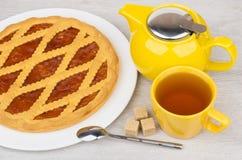 Empanada, tetera, taza de té y pedazos de la torta dulce de azúcar en la tabla Imagenes de archivo