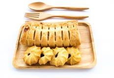 Empanada y galletas de la piña en placa de madera en el fondo blanco Fotografía de archivo
