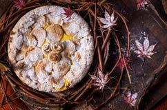 Empanada y pudín de manzana hecha en casa adornados con las hojas de arce y suga pulverizado imagen de archivo