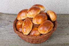 Empanadas con la carne o la col en una cesta de mimbre en un fondo de madera Imagen de archivo libre de regalías