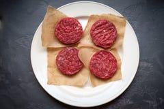 Empanadas crudas para la hamburguesa en una placa blanca en un fondo de piedra foto de archivo