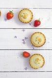 Empanadas de manzana hechas caseras frescas y fresas frescas en el b blanco Fotografía de archivo