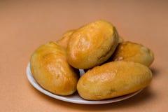 Empanadas frescas con la carne, la col o cualquier relleno Empanadas cocidas en el horno En una placa blanca imagenes de archivo