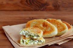 Empanadas fritas rellenas con queso, la cebolla verde y el eneldo Empanadas hechas en casa deliciosas en el fondo de papel y de m Fotos de archivo libres de regalías